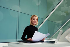 Female secretary with resume of new employees in hands looking at camera in modern office interior Royalty Free Stock Images