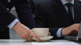 Female secretary serving coffee cup for male director working laptop, assistance. Stock footage stock video footage