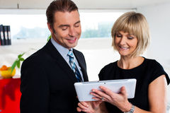 Female secretary showing appointments to boss saved on tablet device Royalty Free Stock Images