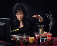 Female seer doing candle wax reading online. Attractive mature female fortuneteller holds yellow burning candle upright over the water in front of monitor Royalty Free Stock Photo