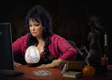 Female seer predicts online with big crystal egg. Portrait of experienced fortuneteller works on-line with big crystal egg. Black haired mature clairvoyant wears Stock Photography