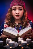 Female seer teller doing psychic reading book. For predicting fate stock photos