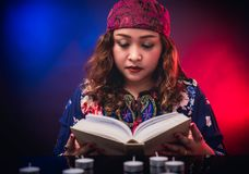 Female seer teller doing psychic reading book. For predicting fate stock image