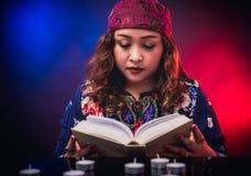 Female seer teller doing psychic reading book. For predicting fate Stock Image