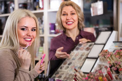 Female selecting hair styiling spray. Young blonde selecting hair styiling spray in beauty shop Stock Photography