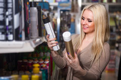 Female selecting hair styiling spray. Young blonde woman selecting hair styiling spray in beauty store Royalty Free Stock Images