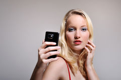 Female selfie. Beautiful blonde haired woman posing for a selphy with her smartphone. Studio shot and a very crisp image Stock Photo