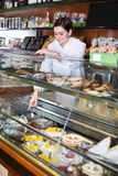 Female seller assisting in choosing dessert Stock Image