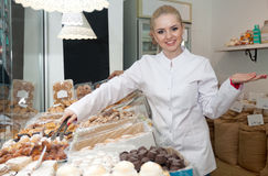 Female seller in confectionery offering sweets. Friendly female seller in local confectionery offering sweets stock images