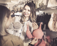 Female seller demonstrating client bras in underwear store Stock Photography