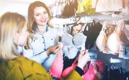 Female seller demonstrating client bras in underwear store Stock Photos