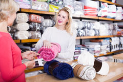 Female seller demonstrating coverlets to senior buyer in textile Royalty Free Stock Photography