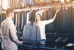 Female seller demonstrating numerous suits Stock Photos