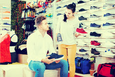 Female seller demonstrating sneakers to customer in sports store Stock Image