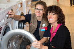 Female Seller helping customer with choosing washing machine royalty free stock images