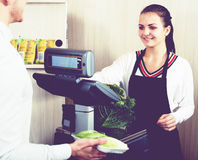 Female seller helping customer to weigh cabbage Royalty Free Stock Images