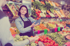 Female seller helping to buy tomatoes Royalty Free Stock Photos