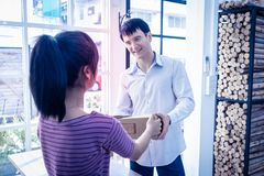 Female home business owner handling package to customer. Female seller home business owner handling package to customer stock photography