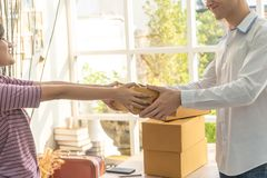Female home business owner handling package to customer stock photography