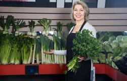 Female seller offering good price for vegetables Stock Image