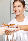 Female seller offering muffins Royalty Free Stock Image