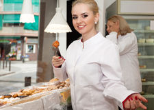 Female seller offering sweets in confectionery. Friendly female seller offering sweets in local confectionery stock photos