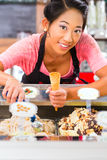 Female seller in Parlor with ice cream cone. Young Asian saleswoman in an ice cream parlor takes a scoop of ice cream Stock Image