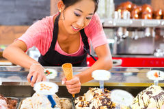 Female seller in Parlor with ice cream cone. Young Asian saleswoman in an ice cream parlor takes a scoop of ice cream Royalty Free Stock Photos