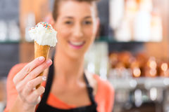 Female seller in Parlor with ice cream cone. Young saleswoman in an ice cream parlor with ice cream cornet Royalty Free Stock Image