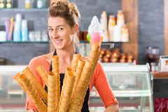Female seller in Parlor with ice cream cone. Young saleswoman in an ice cream parlor with many cones for ice cream cornets Stock Photo