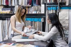 Female seller talking with buyer in store of fabrics and accessories for curtains, interior showroom. Woman looking fabrics for. Curtains upholstery stock photos