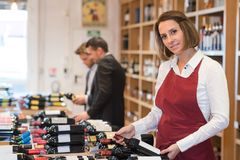 Female seller wearing apron working in wine store. Female royalty free stock photo