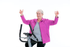 Female senior with arms up train with fitness machine Royalty Free Stock Photography
