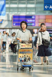 Female senior with baggage trolley at Incheon Airport, South Korea. Stock Photos