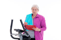 Female senior with clipboard train with fitness machine Royalty Free Stock Photos