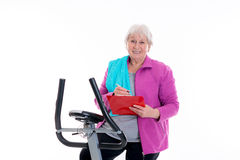 Female senior with clipboard train with fitness machine Royalty Free Stock Images
