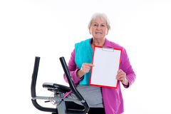 Female senior with clipboard train with fitness machine Stock Images