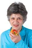 Female senior eating a fresh apple Stock Images