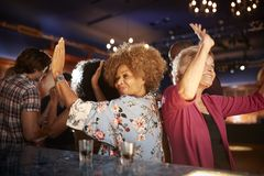 Female Senior Friends Dancing In Bar Together stock photography