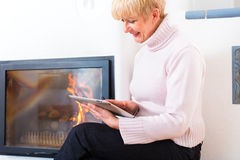 Female Senior at home in front of fireplace. Quality of life - Older Woman or female Pensioner sitting at home in front of the furnace, writing emails on the Royalty Free Stock Photography