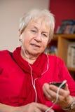 Female senior is listen musik Stock Image