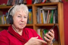 Female senior is listen musik Royalty Free Stock Photos
