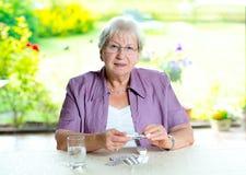 Female senior with a lot of medicament. Older woman with a lot of medicament Royalty Free Stock Images