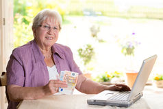 Female senior with money and computer Royalty Free Stock Images