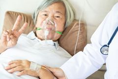 Female senior patient putting inhalation or oxygen mask in hospital bed or home,doctor or nurse intensive care,closeup hand of royalty free stock photography