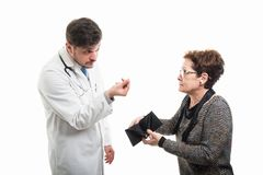 Female senior patient showing empty wallet to male doctor royalty free stock image