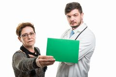 Female senior patient showing green board to male doctor stock images