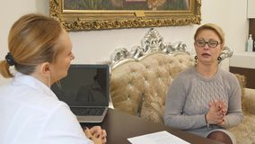 Female senior patient tells the doctor about her health complaints stock footage