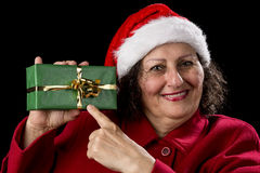 Female Senior Pointing at Green Wrapped Present. Old woman with red coat and Santa Claus hat is smiling. She is pointing her left index finger at a green gift Royalty Free Stock Images