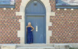 A female senior portrait shoot by a building. A female senior portrait shoot smiles at the camera during a summer shoot in Iowa Stock Photography